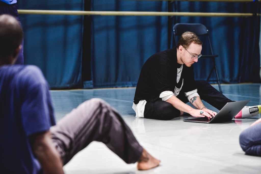 Rob sits on the floor of a dance studio, working on his laptop